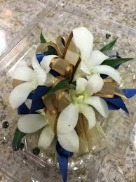 blue and gold ribbon wristlet corsage with white orchids smoke colored rhinestones