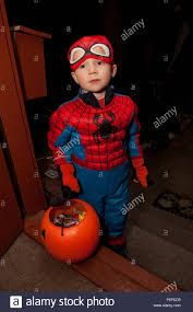 boy in halloween spider man costume with trick or treat stock