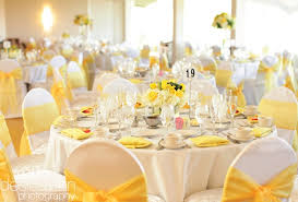 yellow chair sashes white table clothes white chair covers white napkins yellow