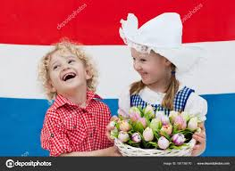 dutch kids with tulip flowers and netherlands flag u2014 stock photo