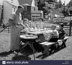 1950s family in backyard cooking dogs sitting at picnic table