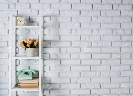 shelf with interior decoration in front of a white brick wall