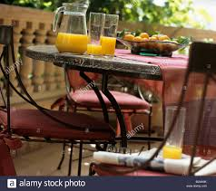 orange juice and bowl of fruit on table on balcony stock photo