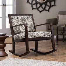 dark brown stained oak wood rocking chair with ethnic accent