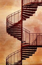 red metal spiral staircase with grungy background stock photo