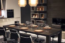 wooden cabinets and dining table grayish blue chair black pendant