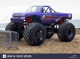 2014 monster jam trucks male sat on wheel of slingshot monster truck to add scale on the
