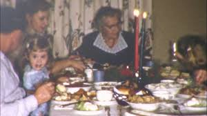 happy family sits at the kitchen table to enjoy turkey dinner