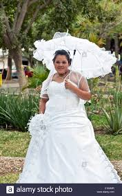 plump smiling bride poses in her wedding dress under shade of