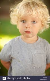 close up portrait of innocent blonde toddler boy with curly hair