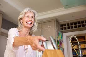 femme plus cuisine femme plus âgée de sourire dans la cuisine avec le bloc de couteau