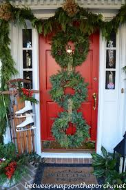 front porch decorated for christmas with three wreaths on door and