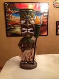solar tikis statue holding a tiki torch from the christmas tree