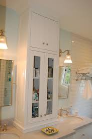 custom white bathroom vanity with tower cabinet between double