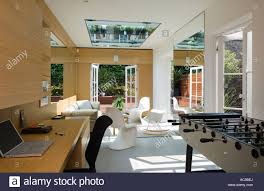 Open Plan by Open Plan Living Room With Large Mirrors And Table Football Stock