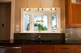 3 cream pendant lamps over black sinks connected by grey tile