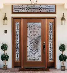 front entry door with wood and glass door and chandelier and trees