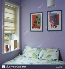pictures above bed with leaf patterned bedlinen in a mauve economy