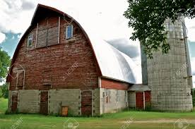 old red round barn with white steel sheets of metal for the roof