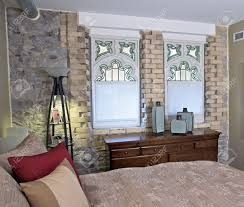 stained glass windows and a stone wall in loft conversion bedroom