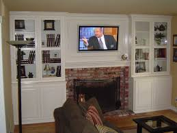 white entertainment center with tv over fireplace cabinet