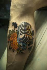 yellow flowers and microphone tattoo on leg by ed tattoo