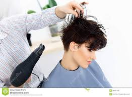 hair stylist using dryer on woman wet hair in salon short hair