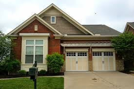 garage door replacement 10 tips for making the right choice the rectangular shape of these garage doors window openings and the division of the windows with square grilles mimic the design of this home s large
