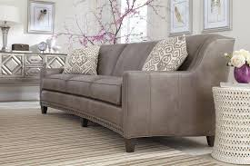 slightly curved sofa with sloping track arms and nail head trim by