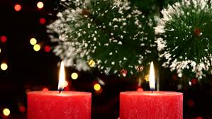 two big red candles with christmas decorations and tree on black