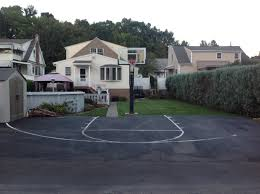 there is his asphalt concrete blacktop in front of the hoop that