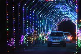 cars ride through a tunnel of lights at the nights of shimmering lights display at