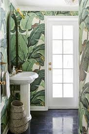 small powder room with banana tree wallpaper and pedestal sink