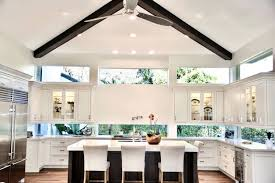white floating cabinets with dark cherry island and wood ceiling