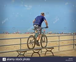 bicycle stunt a man riding his bike over a bench on the boardwalk