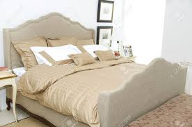 a large comfortable bedroom with a bed and lots of pillows stock
