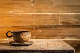 palm wood coffee cup on wooden table and wooden wall stock image