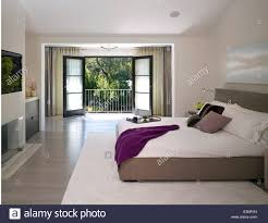 double bed in room with open balcony doors stone house atherton