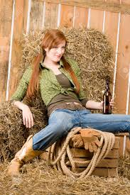 provocative young cowgirl drink beer in barn country style stock