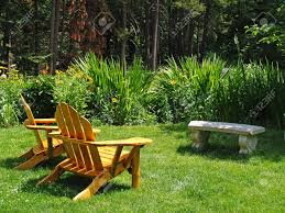 empty adirondack chairs in an green park stock photo picture and