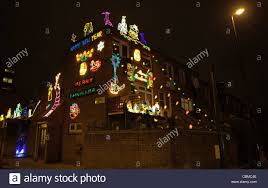 christmas lights and decorations on a house at the corner of roman