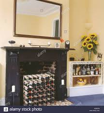 wine storage in fireplace below large mirror in pastel yellow