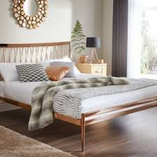 bedroom iron bed frame with white pillows and wooden flooring