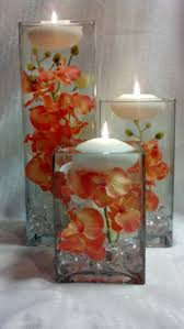 three square vases with coral orchids and floating