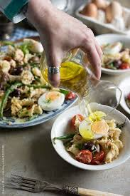 tuna nicoise pasta salad hand pouring olive oil dressing over a