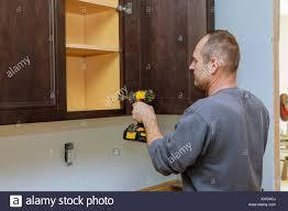 Handyman Kitchen Cabinets Handyman Fixing Kitchen S Cabinet With Screwdriver Adjusting