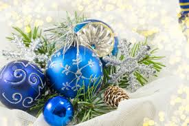blue christmas ornaments and fir tree branch against shiny silver