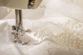ivory wedding dress fabric being sewn on vintage machine stock