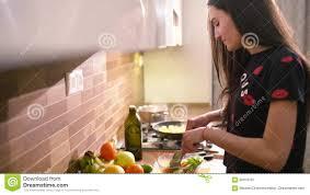 fait de la cuisine la femme aux cheveux noirs heureuse dans des vêtements à la maison