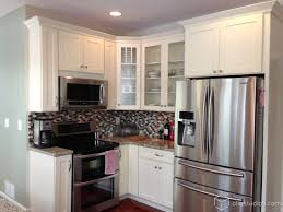 cute white shaker kitchen with an island with barstool seating